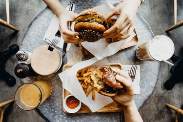 Top view of friends having a good time eating burgers with french fries and drinks in a cafe