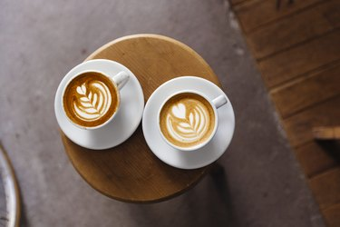 Directly above view of two coffee cups with latte art on the round table