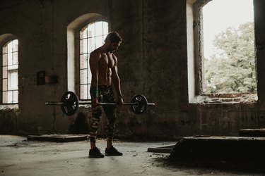 Athletic man holding weights in deadlift in an old building