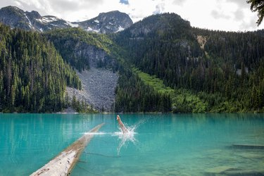 A girl practicing swimming safety dives into the blue waters of Joffre Lakes with mountain background