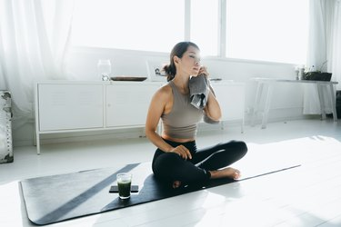 Young Asian woman wiping sweat with a towel after a Bikram yoga session