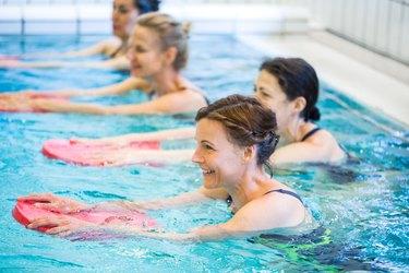 Happy mature females exercising in swimming pool