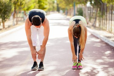 Man and woman outside stretching and trying to touch their toes