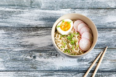 Instant noodles on wooden background. Cooked chinese instant noodles. Soup Ramen with egg and radish.