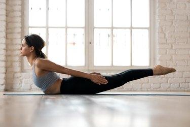 Young sporty woman practicing yoga, doing Double Leg Kicks exercise