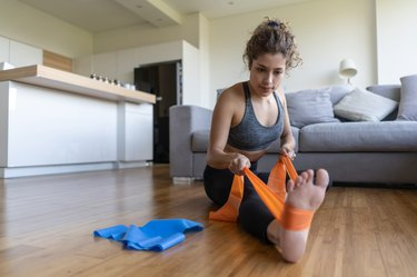 Woman stretching at home using a resistance bands