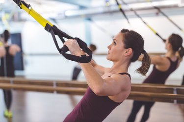 Woman doing full-body TRX workout at the gym