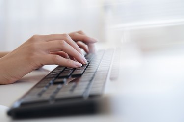 Hispanic businesswoman typing on keyboard