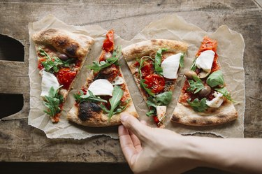 Woman taking healthy pizza recipes from chopping board, overhead view