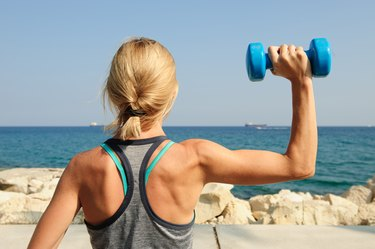 Young athletic woman exercising outdoors: overhead press for upper body strength
