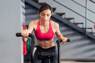 Woman in gym using exercise bike