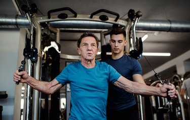 A man with a young trainer doing strength workout exercise in gym.