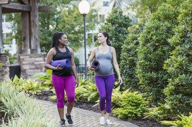 Two multi-ethnic pregnant women walking to yoga class
