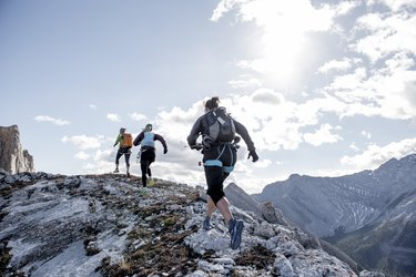 Trail running friends ascend mountain ridge