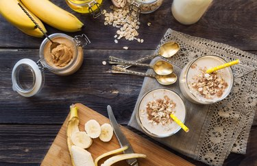 Fresh homemade nutritional smoothie with banana, oat flakes and peanut butter on rustic wooden background with ingredients.