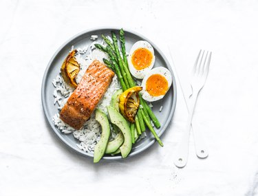 Healthy delicious balanced lunch - baked salmon, rice, asparagus, avocado and boiled egg on a light background, top view