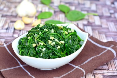Healthy sautéed magnesium-rich spinach with minced garlic in white bowl on kitchen cloth