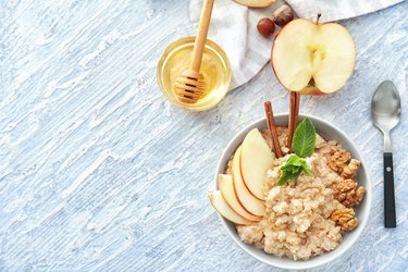Tasty oatmeal with apple and walnut in bowl on table