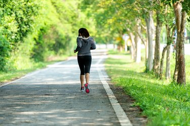 Healthy woman jogging run and workout on road outdoor. Asian runner people exercise gym with fitness session, nature park background. Healthy and Lifestyle Concept.