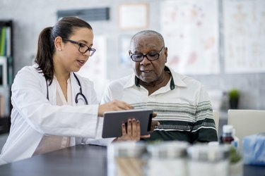 Doctor showing older man his test results on a tablet