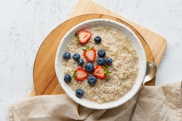 Oatmeal porridge rustic with berries, dash diet, on white wooden background top view