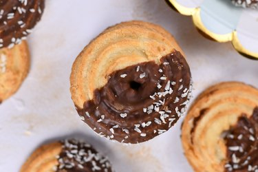 Round ring shaped sweet biscuits with half side glazed with chocolate and topped with coconut sprinkles