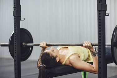 Woman doing bench press in gym