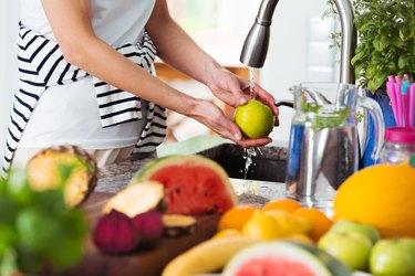 Healthy woman washing apple