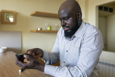 It's time to take better care of myself. African Businessman Doing Blood Sugar Test at Home