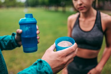 Preparing protein shake outdoors. Close-up.