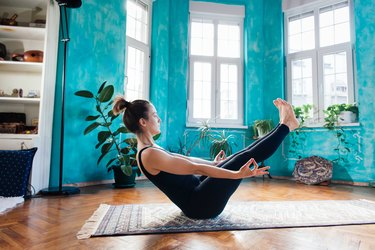 Woman holding boat pose in living room on area rug
