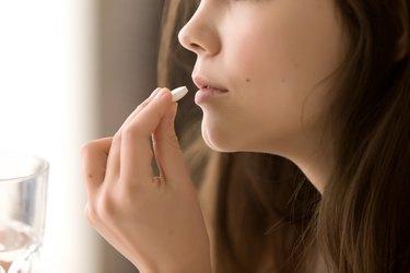 Close up image of woman taking magnesium malate