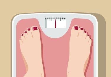 Feet on bathroom scale conveying obesity health risks