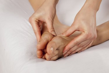young woman massaging her tired feet