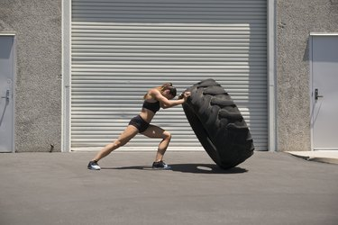 Young woman lifting a giant tire