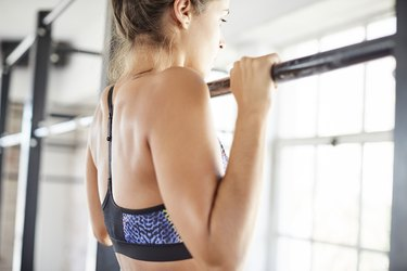 Midsection of female exercising on pull-up bar in gym