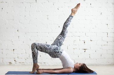 Fitness woman doing one legged bridge pose