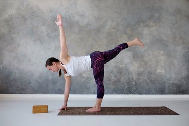 woman practicing yoga in twisted half moon pose in front of gray wall at home
