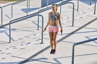 Fit young woman skipping rop outdoors