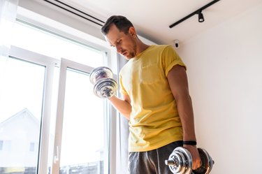 A young guy is training with dumbbells at home