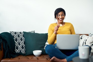 A woman snacking on her couch while using her laptop