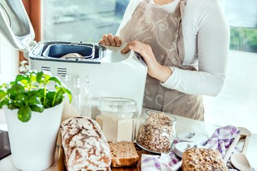 Woman in a modern kitchen among the ingredients for homemade bread prepares a machine for baking