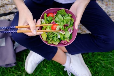 A girl sits on the grass and eats a green fresh salad with chopsticks for sushi.