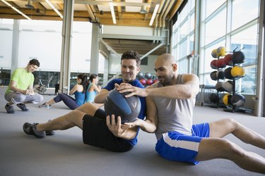 Two men sitting back to back doing medicine ball twist workout at gym