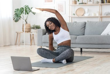 Sporty black girl exercising at home, using laptop