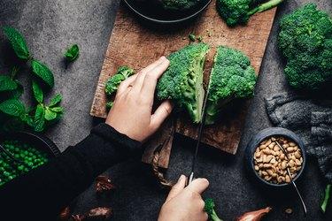 Woman cutting fresh broccoli on cutting board, dark background