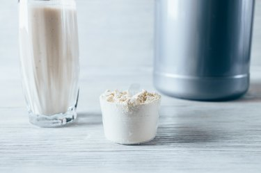 Scoop with dry protein powder, container and glass of drink