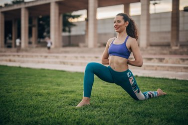 woman in sports bra and leggings doing hip stretches in the park