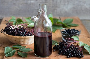 A bottle of elderberry syrup on a wooden table