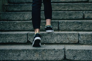 The girl in black jeans climbs on concrete stairs